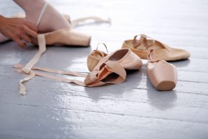 Ballerina's slippers lying on the floor while she is trying them on